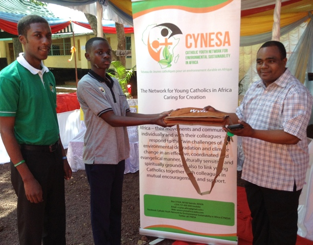Fr Kadio presents a gift to a participant after an ecoquiz sponsored by CYNESA.